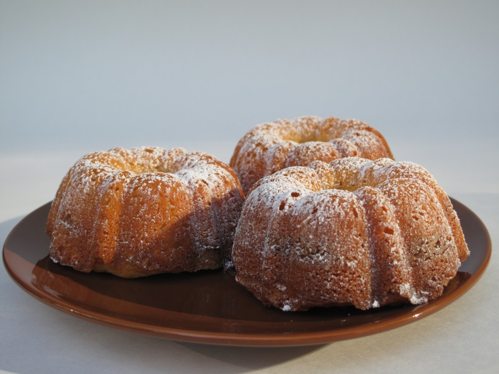 3 Cinnamon Swirl mini bundt cakes on a brown plate. Fluted cakes dusted with powdered sugar.