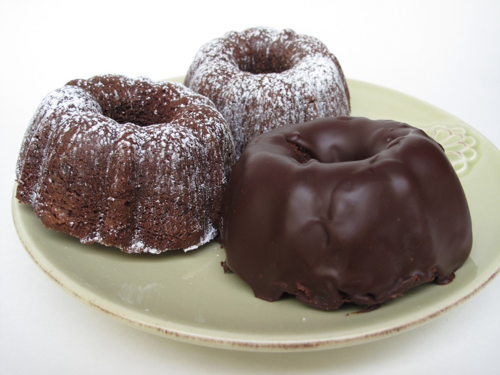 3 Chocolate Buttermilk Mini Bunt Cakes on a green plate. Two cakes are covered in powdered sugar and one is coated in chocolate ganache.