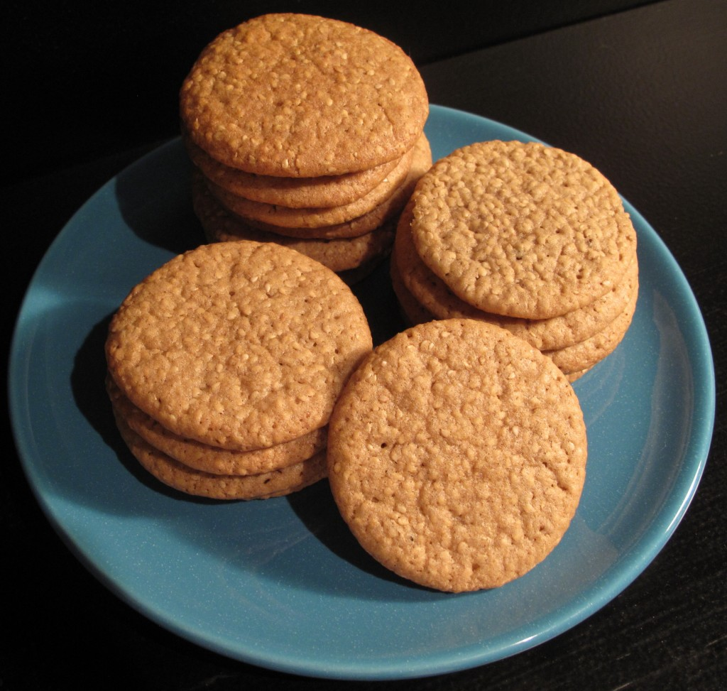 Good Luck Sesame Benne Wafers, thin, golden cookies speckled with sesame seeds, stacked on a blue serving plate.