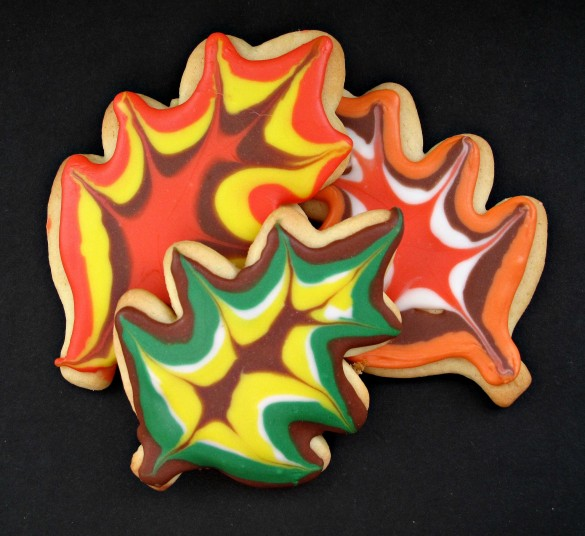 Three Decorated Thanksgiving Sugar Cookies look like oak leaves.