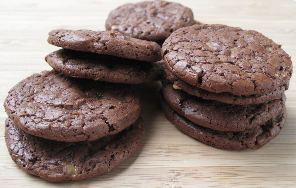 Chocolate Toffee Cookies piled on brown wood cutting board