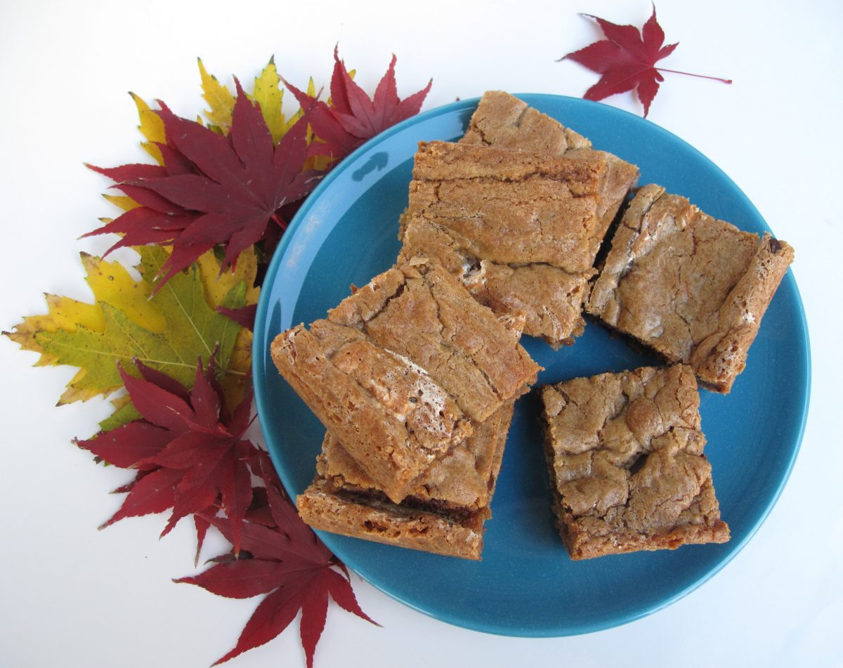 Chewy Chocolate Toffee Marshmallow Cookie Bars on a blue plate with colorful fall leaves.