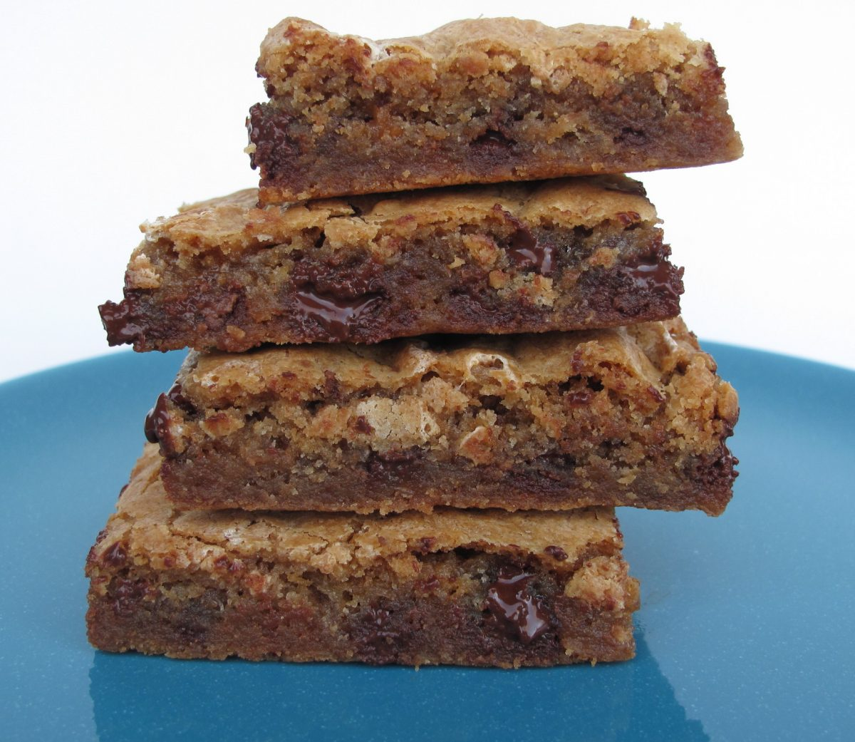 Stack of Chewy Chocolate Toffee Marshmallow Cookie Bars on a blue plate.