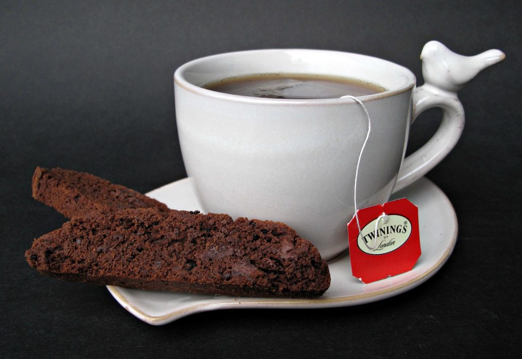 Chocolate Espresso Biscotti on the edge of a sauce with a cup of tea.