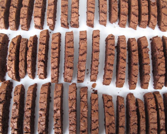 Sliced biscotti lined up in three rows on a baking sheet.