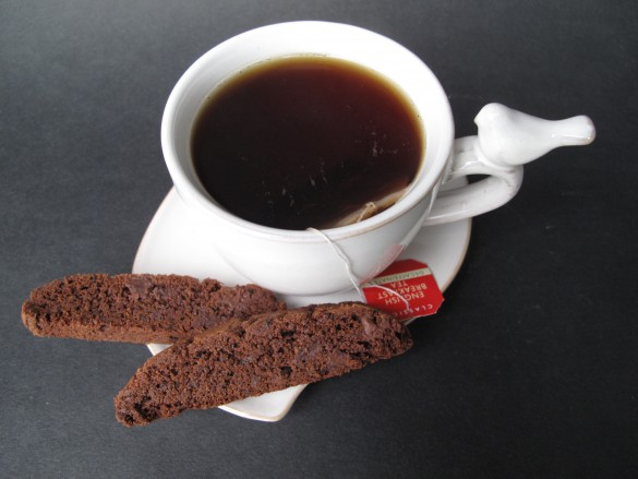 Biscotti on a saucer with a cup of tea from above.