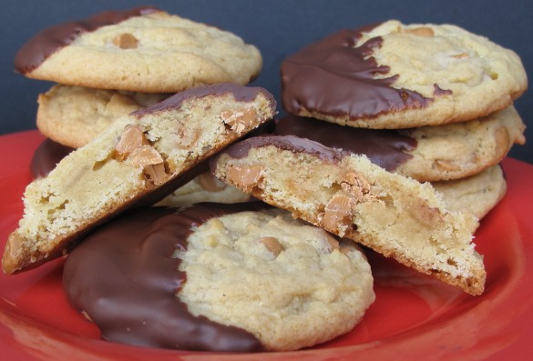 Banana Chip Butterscotch Pudding Cookies on a red plate with one cut in half to show interior.
