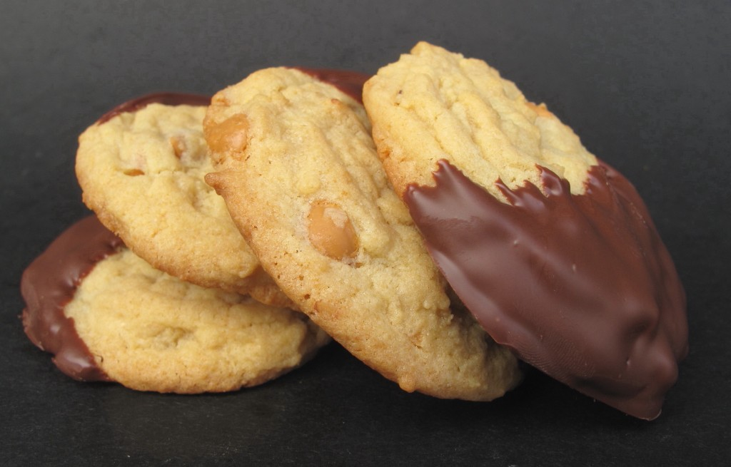 A pile of Banana Chip Butterscotch Pudding Cookies each half dipped in chocolate.