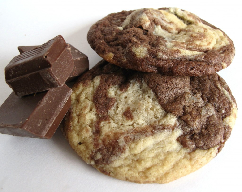 Marbled Chocolate Chunk Cookies on a white background with chunks of chocolate.