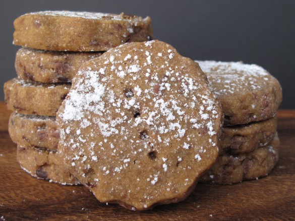 One cookie dusted in powdered sugar in front of two piles of cookies