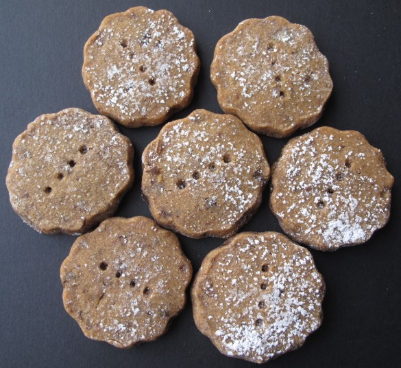 Seven Espresso Chocolate Shortbread Cookies dusted in powdered sugar on a black background