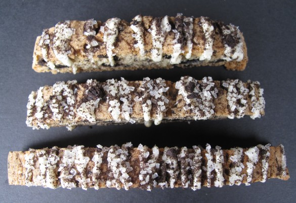 Three Oreo Biscotti drizzled with icing and sprinkled with sugar and crushed cookies.