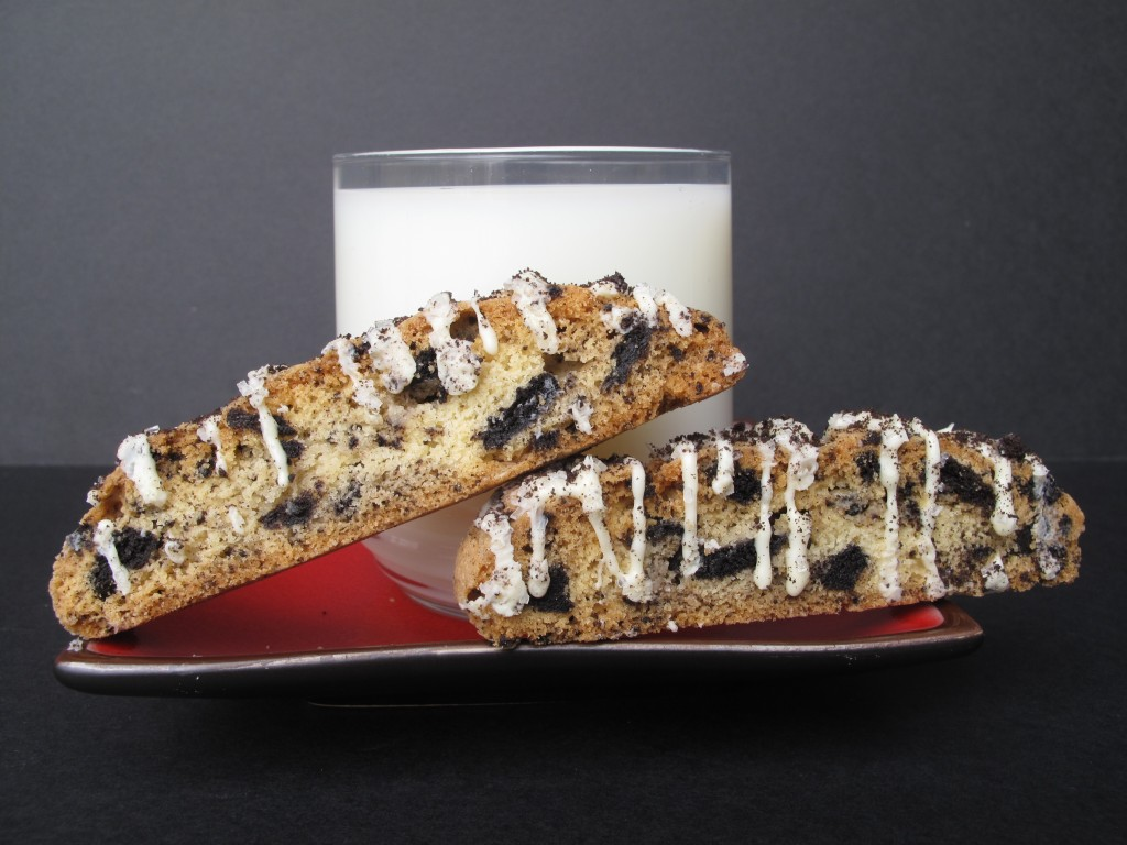 Oreo Biscotti on a red plate with a glass of milk.
