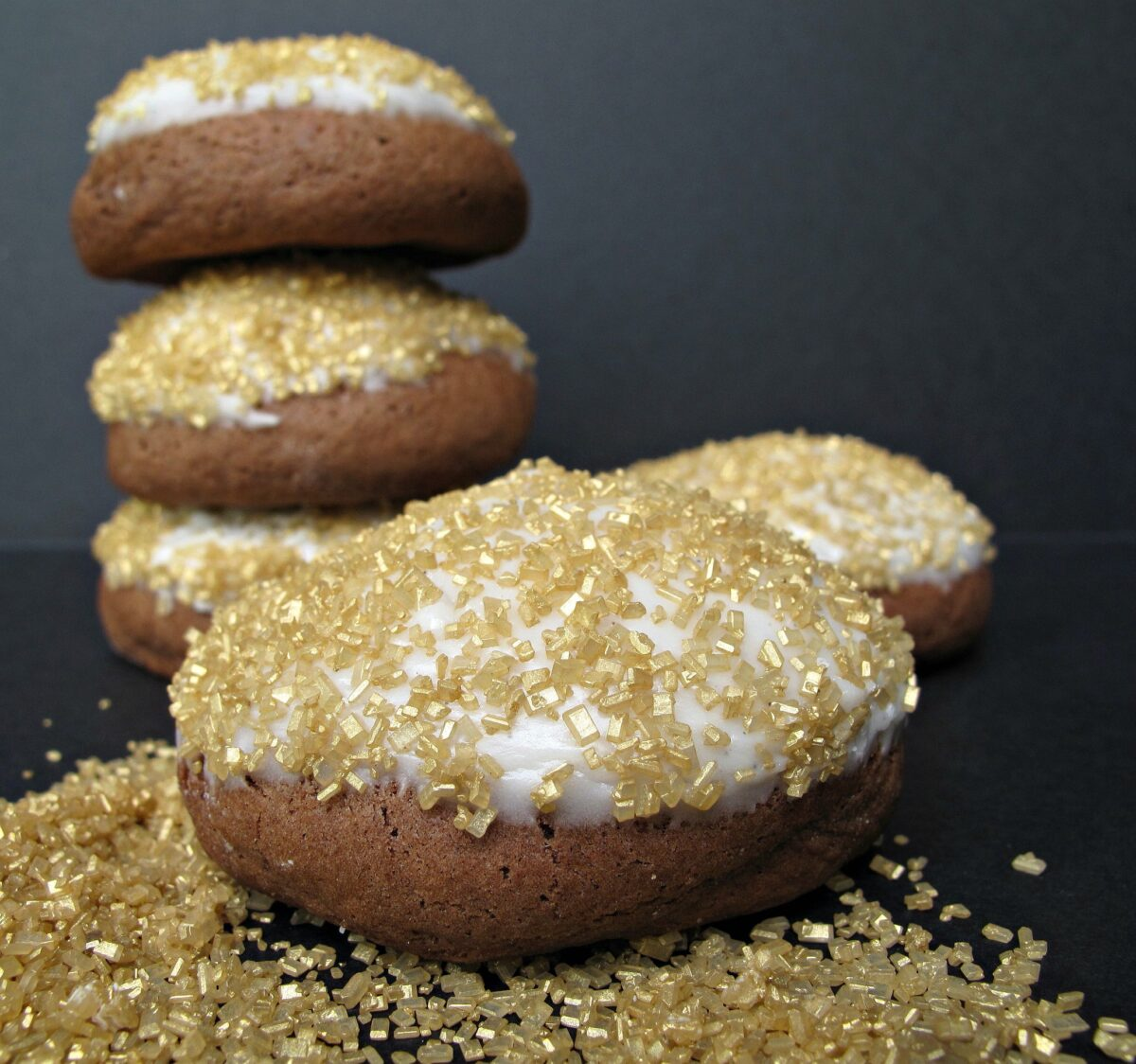 Closeup of chocolate cookie topped with white icing and gold sugar  and a cookie stack in background.