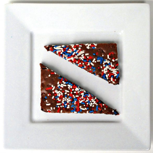 Two triangles of Patriotic Brownie Crunch on a square white plate.
