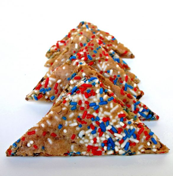 Triangular chocolate chip cookie crisps sprinkled with red, white and blue jimmies, lined up in a row.