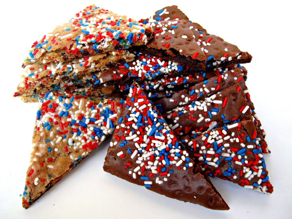 Two piles of brittle. On the left are chocolate chip cookie brittle triangles and on the right are brownie brittle triangles. Both are sprinkled with red, white, and blue.