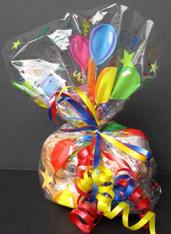 Cinnamon Sugar Twist Cookies wrapped for gift giving in a brightly colored cellophane bag tied with red, yellow and blue curling ribbon.
