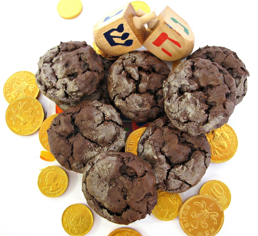 Puffy Chanukah Gelt Cookies, with a crackled top dusted in golden glitter dust in a pile with gold foil chocolate coins and two dreidles
