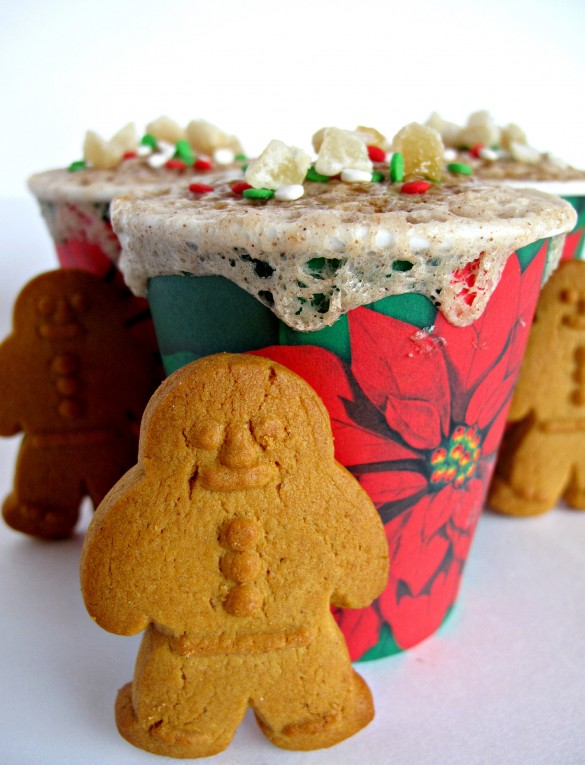Gingerbread cookie standing in front of a 3-2-1 Gingerbread Cake with Crystallized Ginger and Caramel Syrup in a poinsettia paper cup