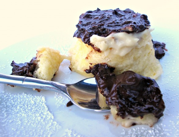 a spoonful of chocolate covered Boston Cream Pie Mug Cake with the cake in the background