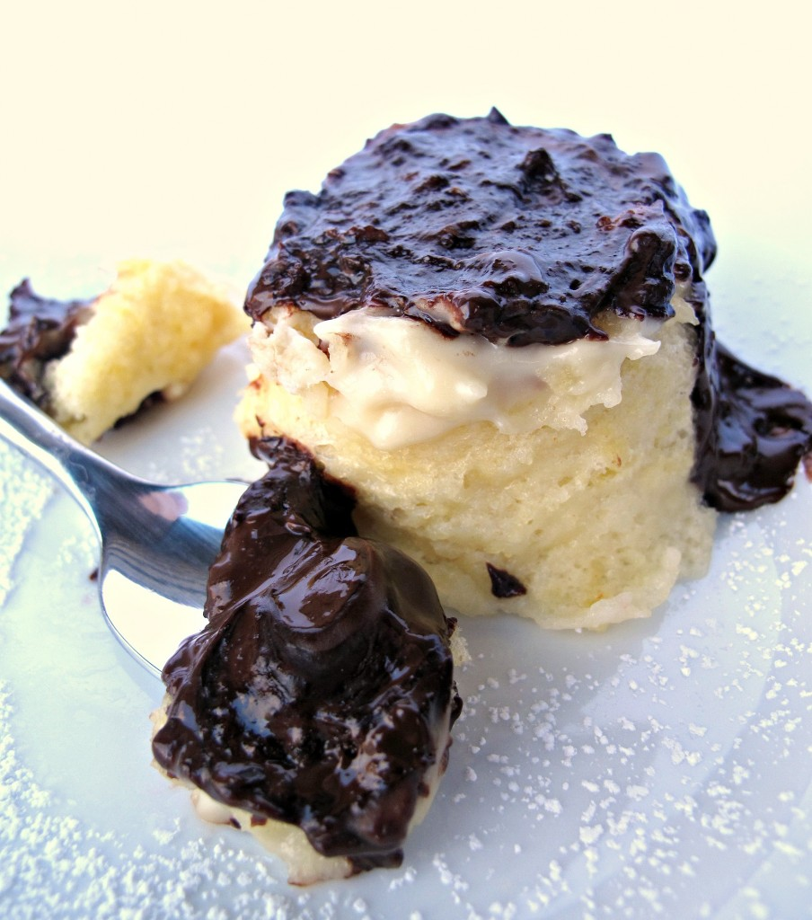 Boston Cream Pie Mug Cake on a plate behind a spoon full of cake covered in melted chocolate