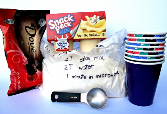 Ingredients for Boston Cream Pie Mug Cake including cake mix, pudding, chocolate candy, tablespoon, paper cups