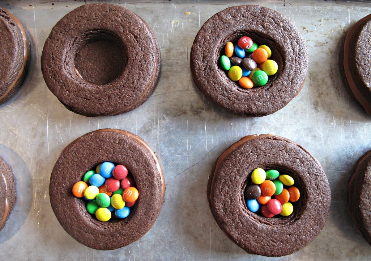Piled chocolate sugar cookie circles with candy at the center.