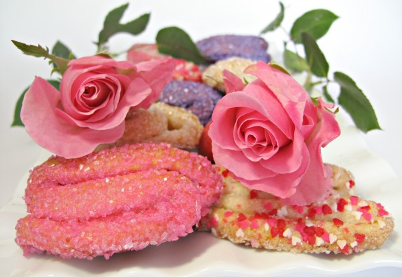 Rose Bud Butter Cookies, one coated in pink sugar and another coated in heart sprinkles and two pink roses
