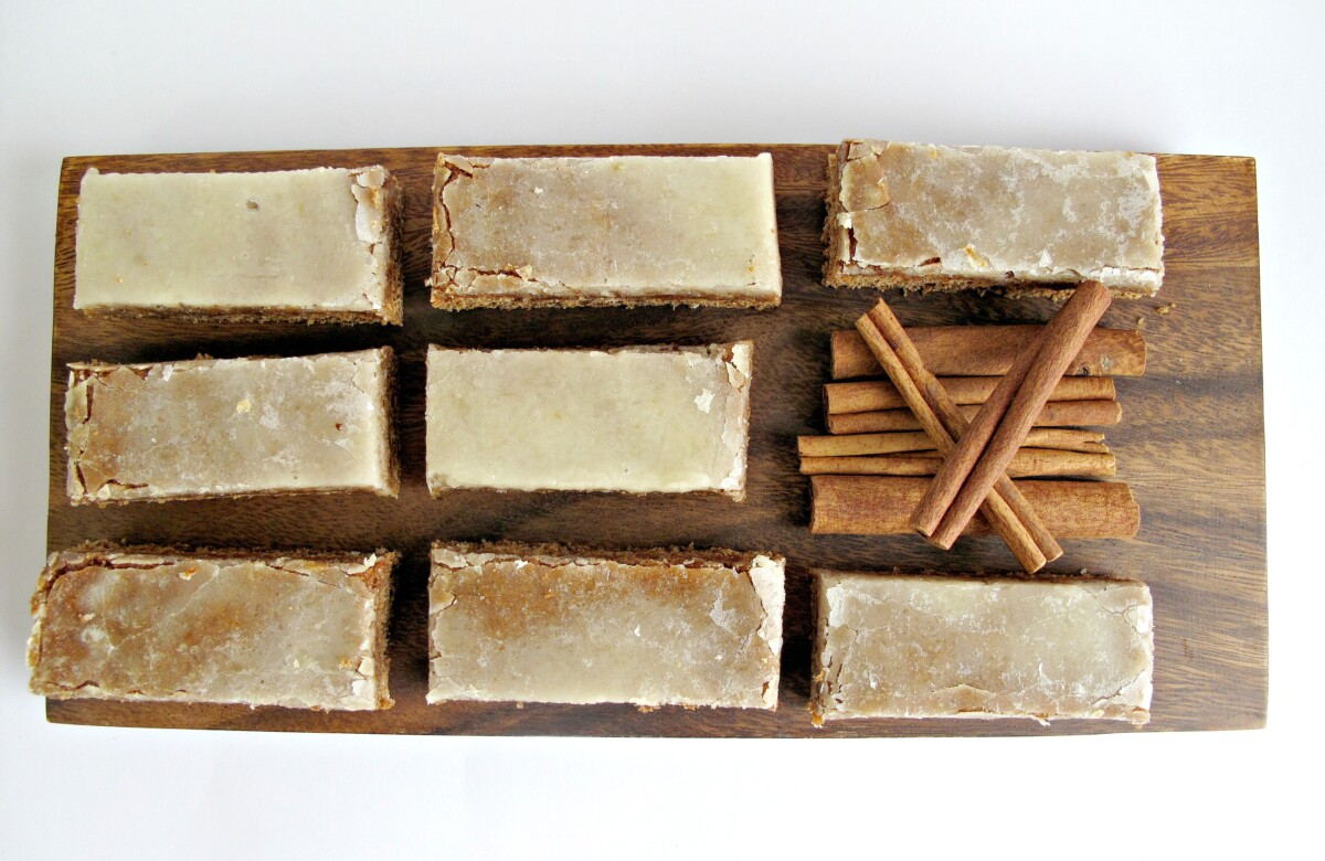 Overhead view of iced Lebkchen bars with a pile of cinnamon sticks.