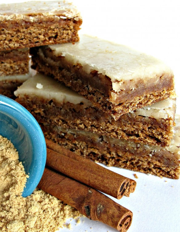 Chewy Cinnamon Ginger Lebkuchen Bars with Orange-Ginger Glaze stacked next to cinnamon sticks and ginger powder, the main flavors in these bars