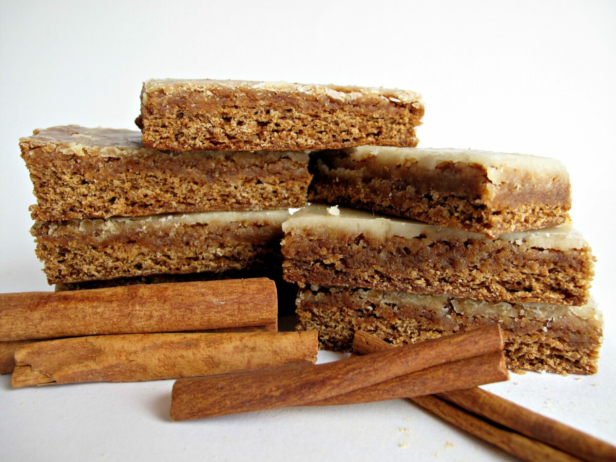 Two stacks of iced Lebkuchen bars next to some cinnamon sticks.