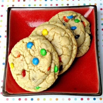Three M&M cookies on a red plate on top of a polka dotted background.