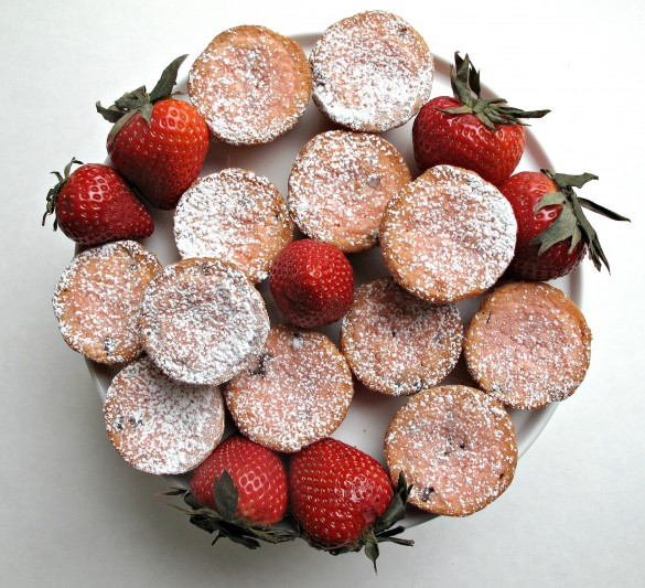 Chocolate Strawberry Blondie Bites topped with powdered sugar and large red strawberries on a round platter