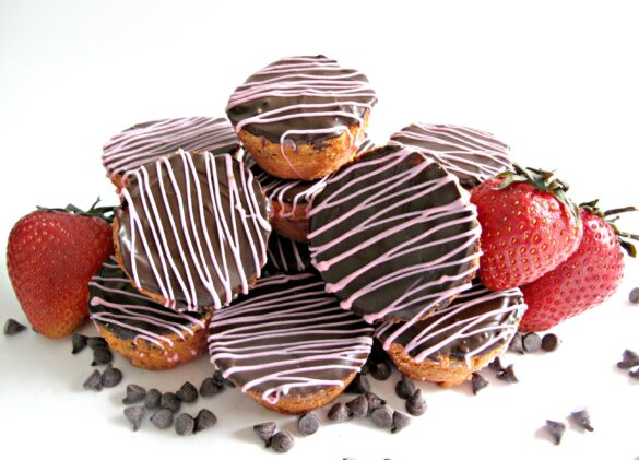 Chocolate Strawberry Blondie Bites in a pile with mini chocolate chip and strawberries. The blondie bites are covered on top with chocolate and a pink zigzag.
