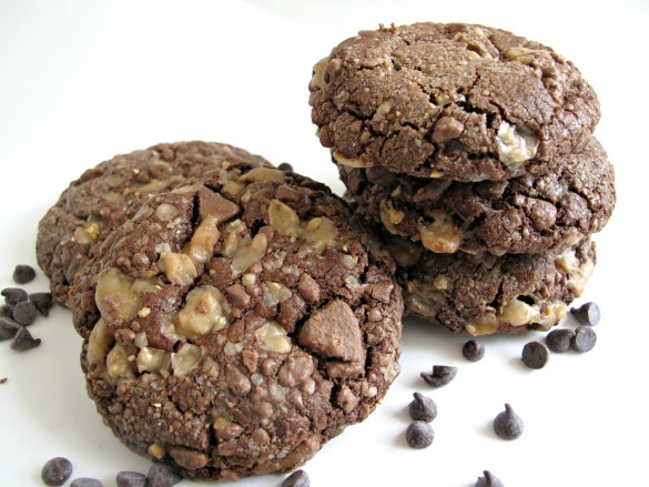 Soft Chocolate-Toffee Cookies in two piles on a white surface with chocolate chips