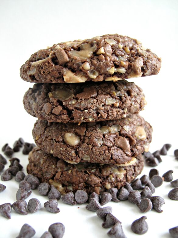 Soft Chocolate-Toffee Cookies in a stack surrounded by chocolate chips