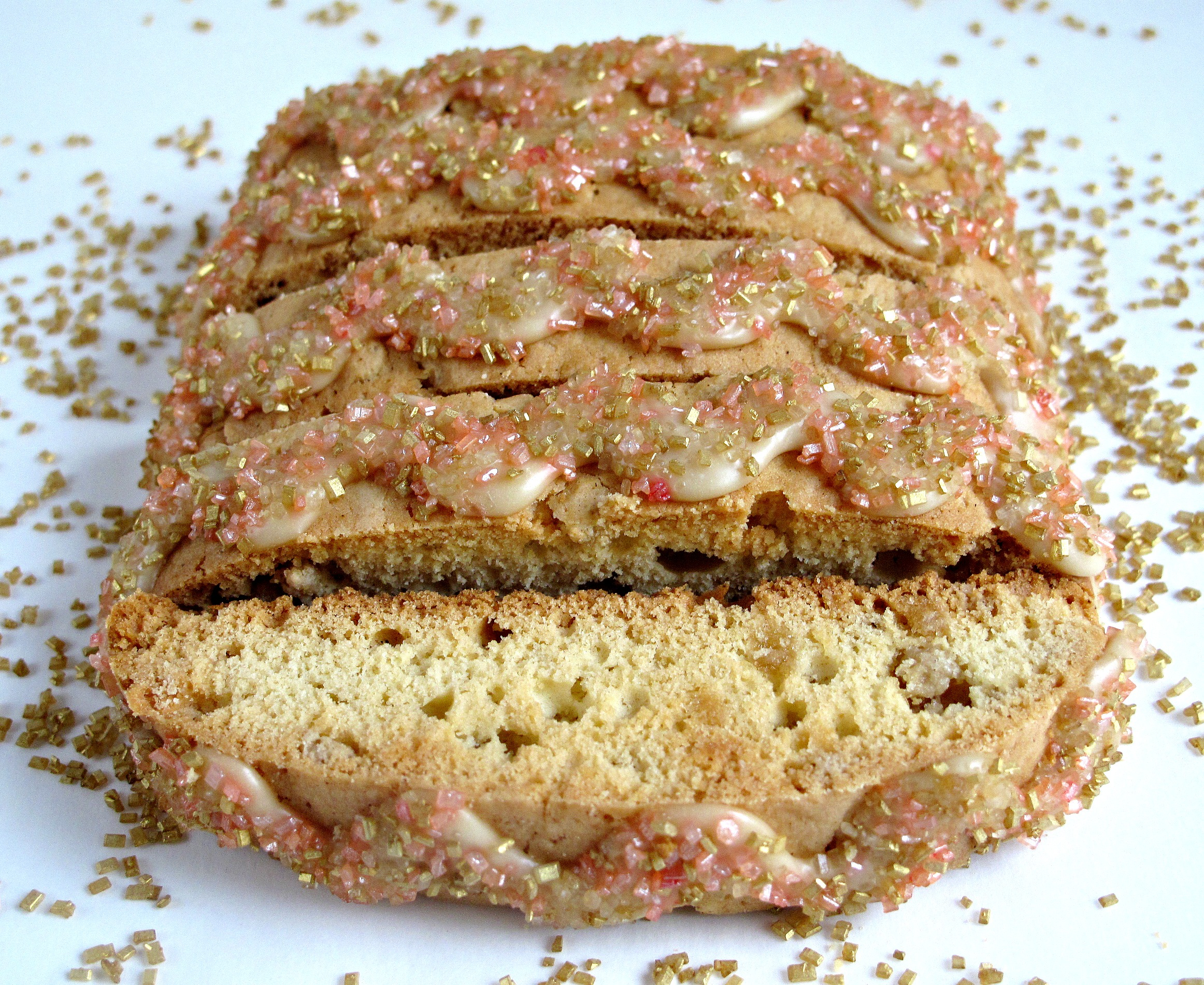 Maple Biscotti with zigzagged maple icing and gold and pink shimmering sugar on top.