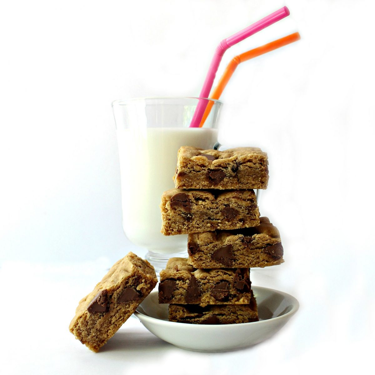 Stack of bars in a bowl in front of a glass of milk with two straws.