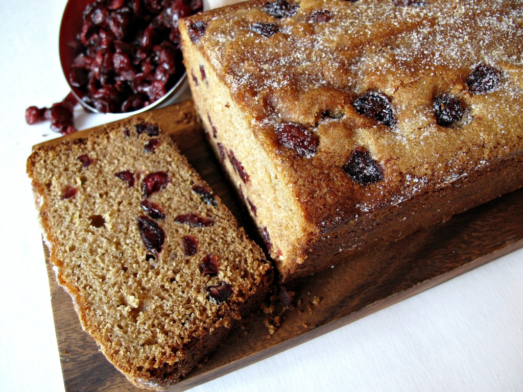 A loaf of Cranberry Clementine Whole Wheat Quick Bread with one piece sliced.
