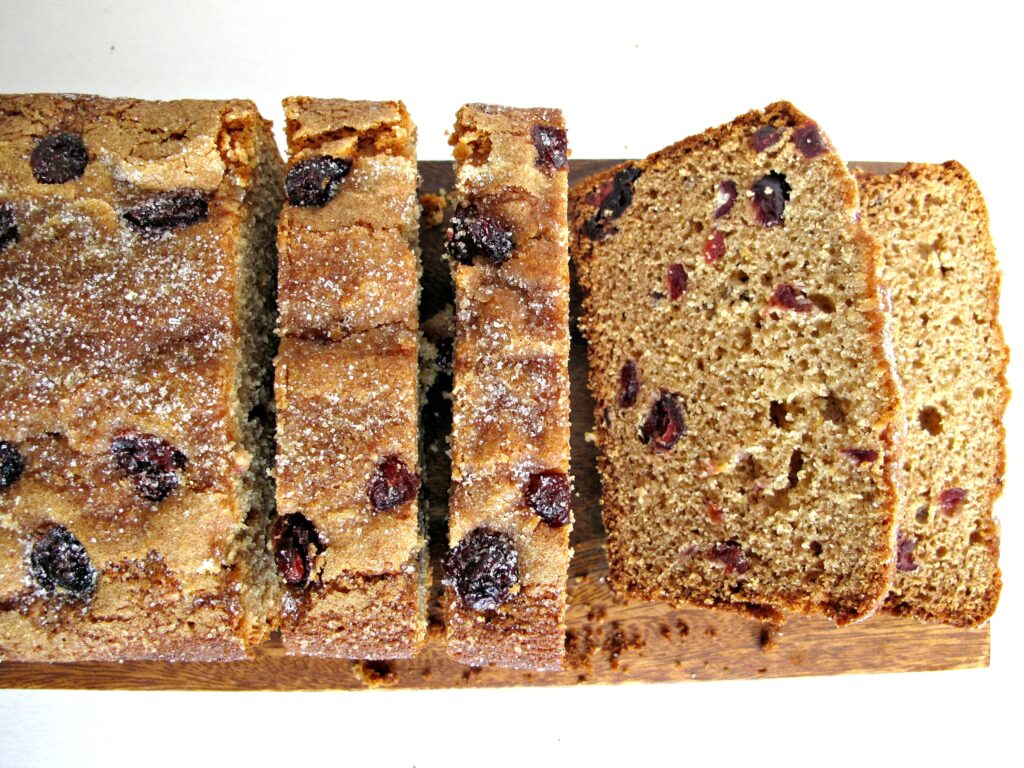 Cranberry-Clementine Whole Wheat Quick Bread sliced on a cutting board