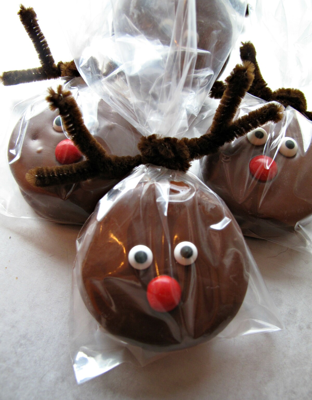 Three Chocolate Covered Oreos decorated to look like Rudolph the Red Nosed Reindeer.