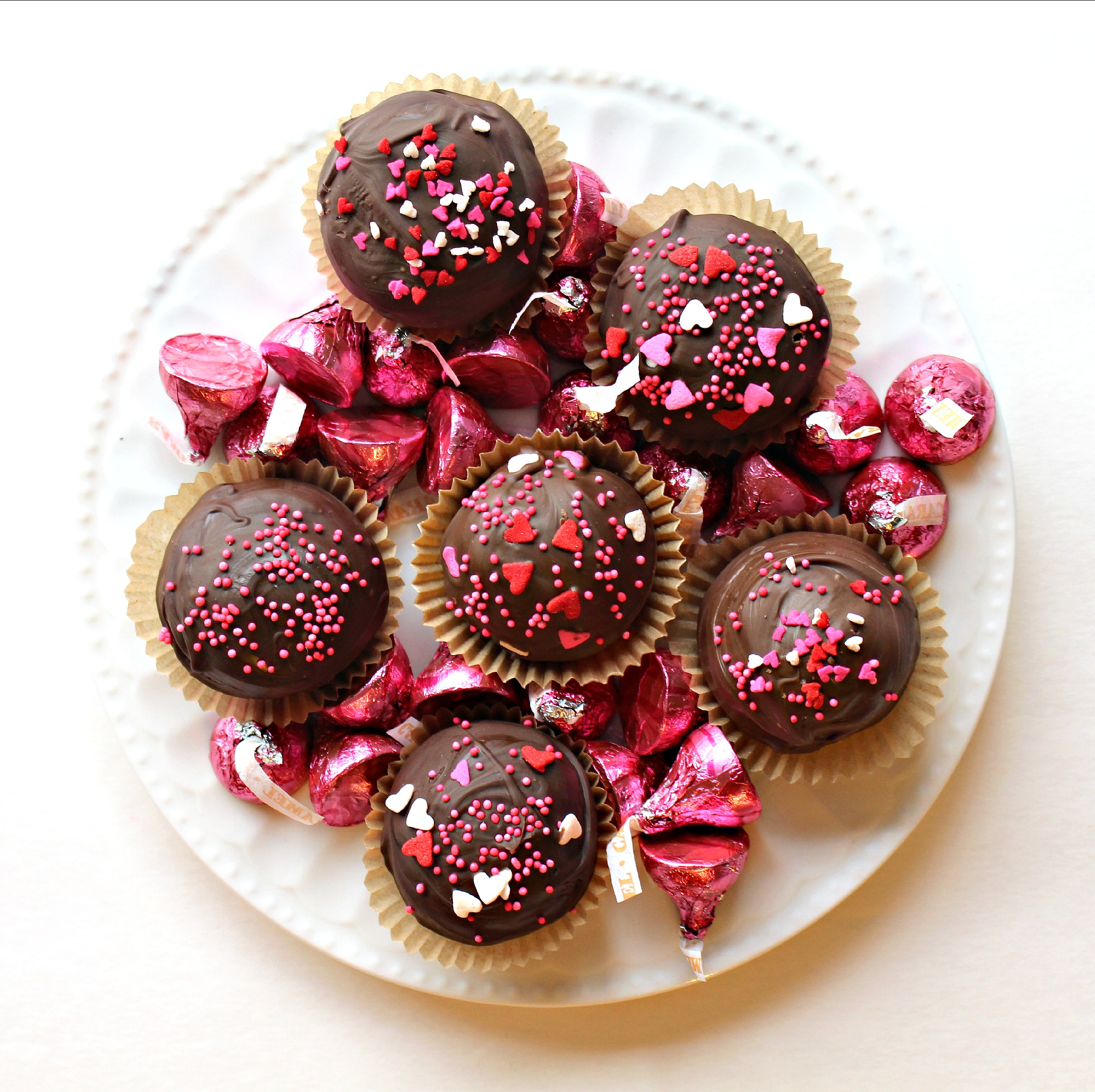 Kiss Cookies from above showing the red and pink nonpareils and heart sprinkles topping the chocolate coated cookies.