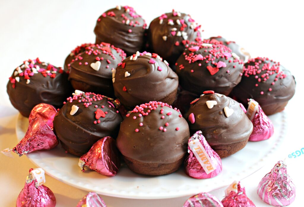 Kiss Cookies piled on a white plate with chocolate Kiss candy wrapped in pink foil. The cookies are ball shaped and covered in chocolate and pink and red Valentine sprinkles.