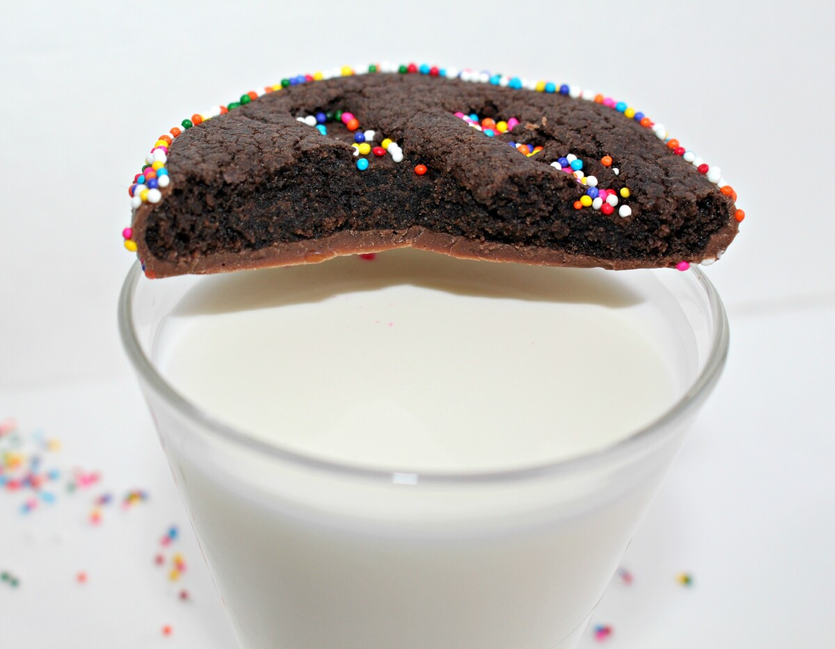 Half of a chocolate cookie on the rim of a glass of milk.