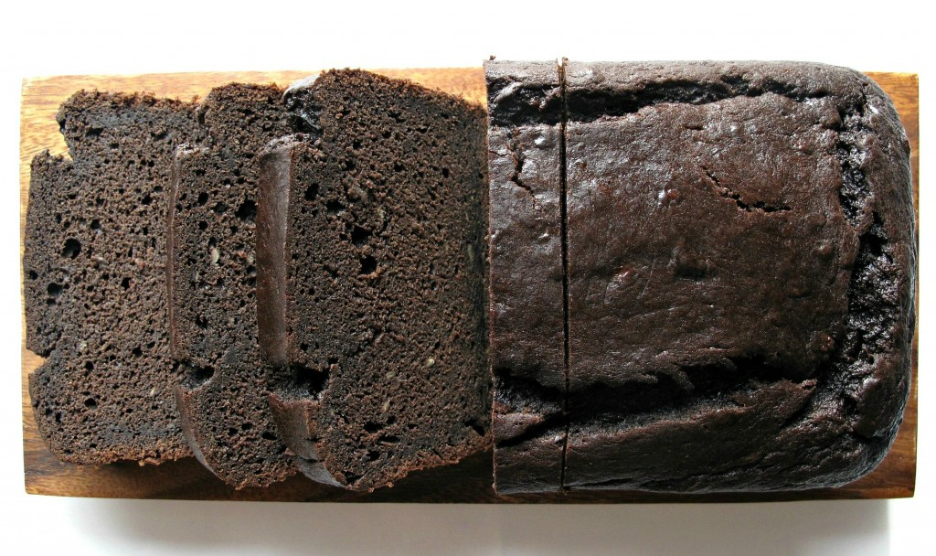 Chocolate-Maple Banana Bread on cutting board sliced to show dark brown dense interior