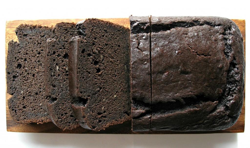 Chocolate-Maple Banana Bread on cutting board sliced to show dark brown dense interior