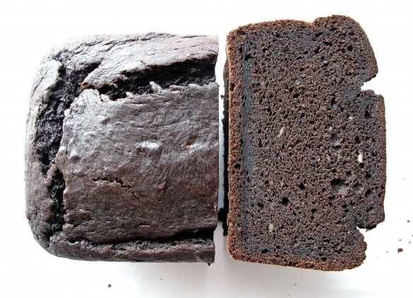 Stack of Chocolate-Maple Banana (or not) Bread slices showing dense chocolate crumb next to shiny topped half loaf