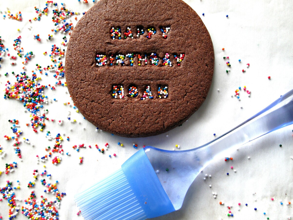 Chocolate cookie, sprinkles, and a pastry brush.
