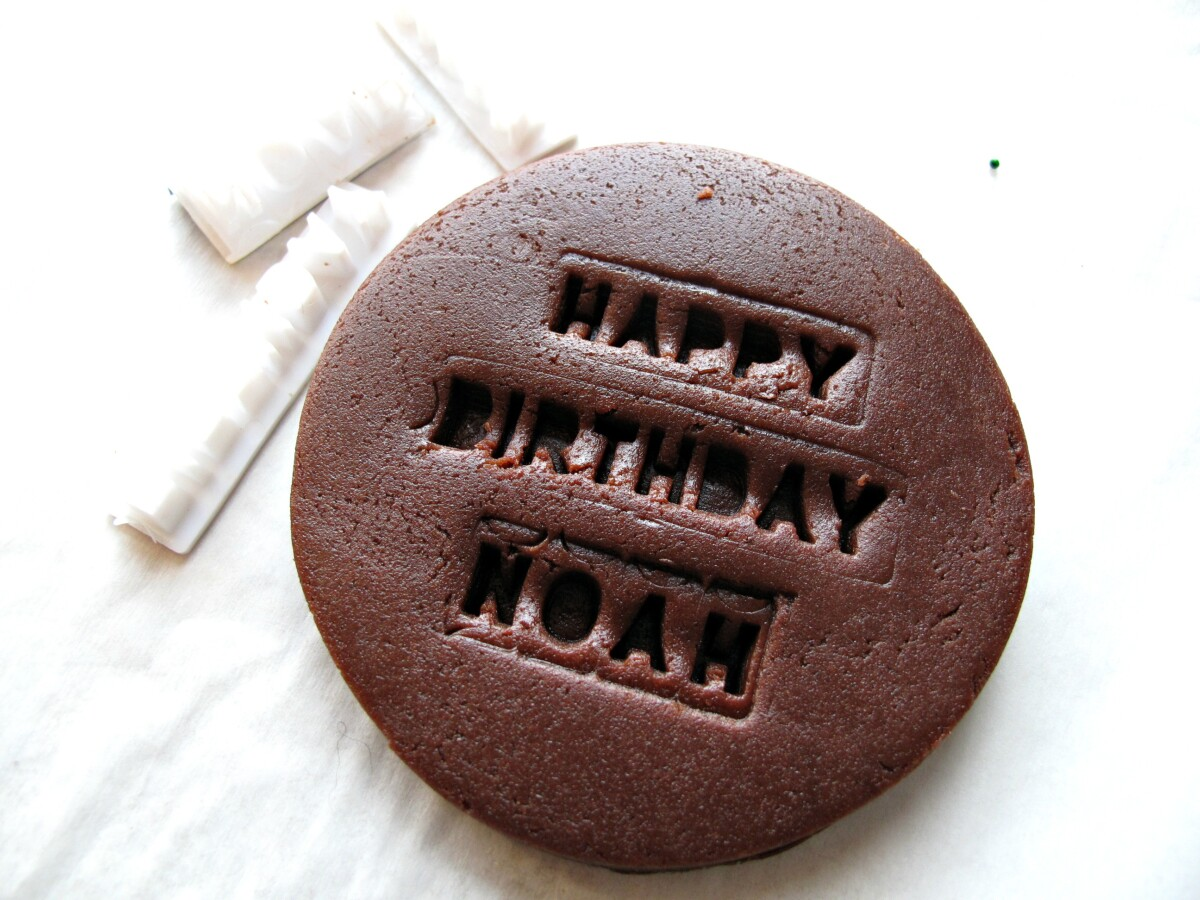 A chocolate cookie with words imprinted in the dough and the plastic imprinting tools.
